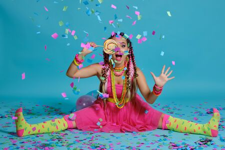 Lovely girl with a multi-colored braids hairstyle and bright make-up, posing in studio with lollipop, air balloons and confetti against a blue background.