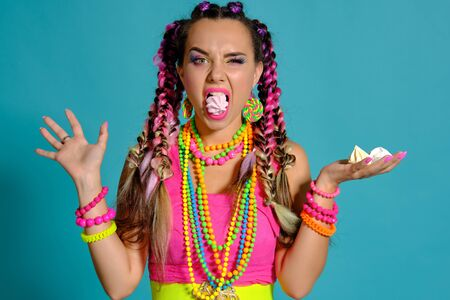 Lovely girl with a multi-colored braids hairstyle and bright make-up, posing in studio against a blue background, holding marshmallow in her hands. Stockfoto
