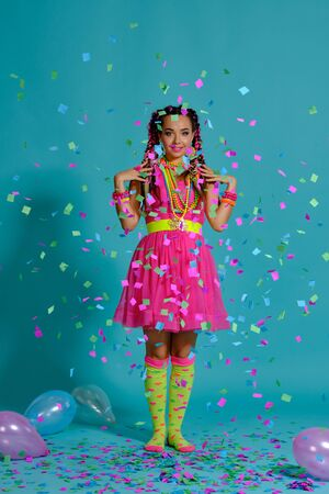 Lovely girl with a multi-colored braids hairstyle and bright make-up, posing in studio with air balloons and confetti against a blue background.