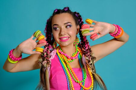 Lovely girl with multi-colored braids hairstyle and bright make-up, holding macarons between her fingers, posing in studio against a blue background. Stockfoto