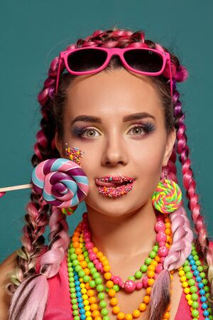 Lovely girl with a multi-colored braids hairstyle and bright make-up, posing in studio against a blue background, holding a lollipop in her hand.