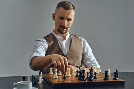 Man with stylish mustache, dressed in brown vest, white shirt is playing chess. Nearby is a cup of coffee. Grey background, close-up. Banque d'images