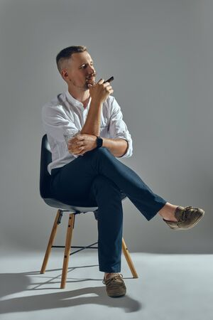 Man with a stylish mustache, dressed in a classic white shirt and dark trousers is sitting on chair, enjoying cigar. Grey background.