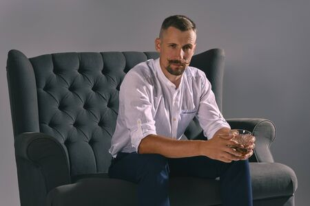 Man with stylish mustache, dressed in white shirt, blue trousers is sitting on dark sofa, holding glass of whiskey, cigar. Grey background, close-up. 写真素材