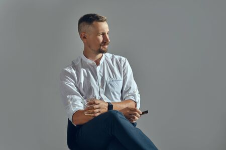 Man with a stylish mustache, dressed in a classic white shirt and dark trousers is sitting on chair, enjoying cigar. Grey background, close-up. Stock Photo