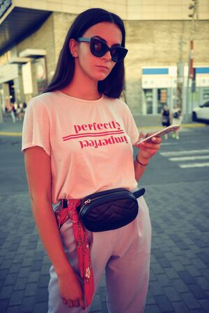 Portrait of a girl in sunglasses posing near a city mall, using smartphone. Dressed in white t-shirt, blue trousers, black waist bag, red kerchief. Stock Photo