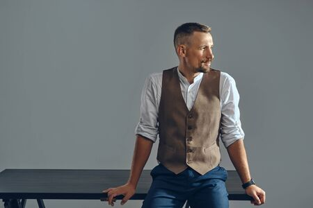Man with a stylish mustache, dressed in brown vest, white shirt and dark trousers is posing sitting on table. Grey background, close-up.