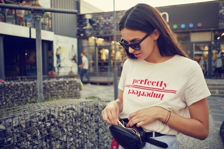 Portrait of a girl in dark sunglasses posing near a city mall. Dressed in white t-shirt, blue trousers, black waist bag, red kerchief.