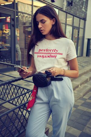 Portrait of a girl posing near a city mall, using smartphone. Dressed in white t-shirt, blue trousers, black waist bag, red kerchief.