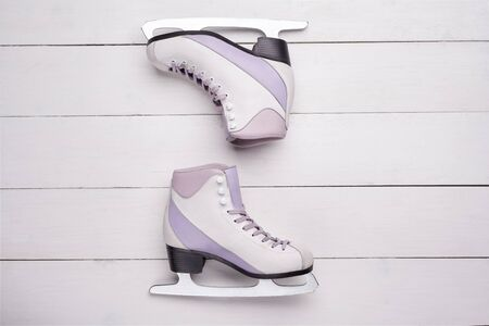 Close-up photo of professional ice skates made of combined leather lying on a white wooden background. The concept of sports, recreation, leisure.
