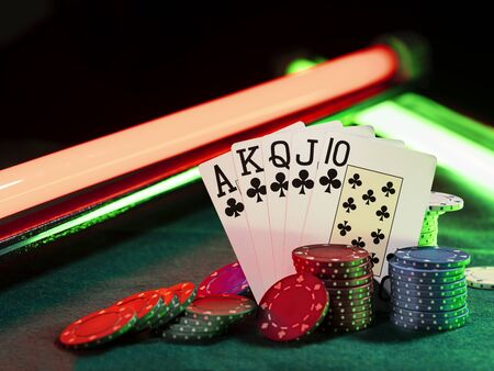 Close-up photo of the winning combination in poker standing leaning on multicolored chips piles, some of them are laying nearby on a green cover of a playing table, against black background, under green and red neon lights. Gambling entertainment, playing cards, casino concept. Stock Photo