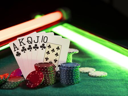 Close-up photo of the winning combination in poker standing leaning on colorful chips piles, some of them are laying nearby on a green cover of a playing table, against black background, under green and red neon lights. Gambling entertainment, playing cards, casino concept.