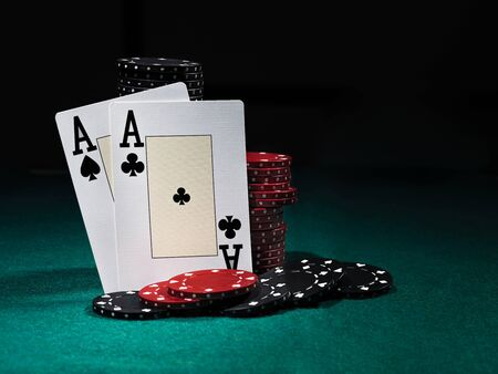 Close-up photo of two aces standing leaning on chips piles, some of them are laying nearby on a green cover of a playing table, against black background. Gambling entertainment, playing cards, poker, casino concept.