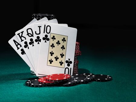 Close-up photo of the winning combination in poker standing leaning on chips piles, some of them are laying nearby on a green cover of a playing table, against black background. Gambling entertainment, playing cards, casino concept. Stock Photo
