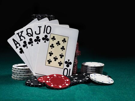 Close-up photo of royal flush standing leaning on chips piles, some of them are laying nearby on a green cover of a playing table, against black background. Gambling entertainment, playing cards, casino concept.