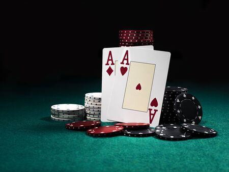 Close-up photo of two aces hearts and diamonds standing leaning on chips piles, some of them are laying nearby on a green cover of a playing table, against black background. Gambling entertainment, playing cards, poker, casino concept.