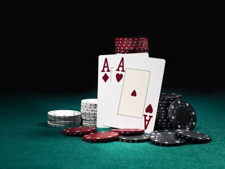Close-up photo of two aces hearts and diamonds standing leaning on colorful chips piles, some of them are laying nearby on a green cover of a playing table, against black background. Gambling entertainment, playing cards, poker, casino concept. Stock Photo