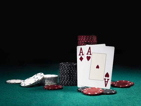 Close-up photo of two aces hearts and diamonds standing leaning on multicolored chips piles, some of them are laying nearby on a green cover of a playing table, against black background. Gambling entertainment, playing cards, poker, casino concept.