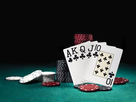 Close-up photo of the winning combination in poker standing leaning on multicolored chips piles, some of them are laying nearby on a green cover of a playing table, against black background. Gambling entertainment, playing cards, casino concept.