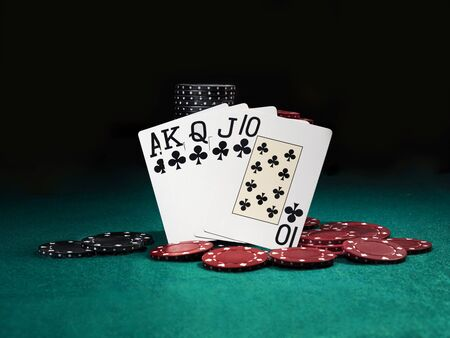 Close-up photo of the winning combination in poker standing leaning on colored chips piles, some of them are laying nearby on a green cover of a playing table, against black background. Gambling entertainment, playing cards, casino concept.