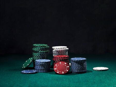 Close-up shot of a colorful chips piles, some of them are laying nearby on a green cover of a playing table, against black background. Gambling entertainment, poker, casino concept.