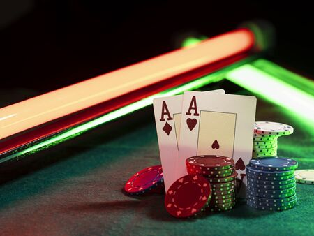 Close-up photo of two aces hearts and diamonds standing leaning on multicolored chips piles, some of them are laying nearby on a green cover of a playing table, against black background, under green and red neon lights. Gambling entertainment, playing cards, poker, casino concept.