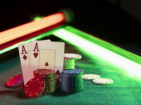 Close-up photo of two aces hearts and diamonds standing leaning on colorful chips piles, some of them are laying nearby on a green cover of a playing table, against black background, under green and red neon lights. Gambling entertainment, playing cards, poker, casino concept. Stock Photo