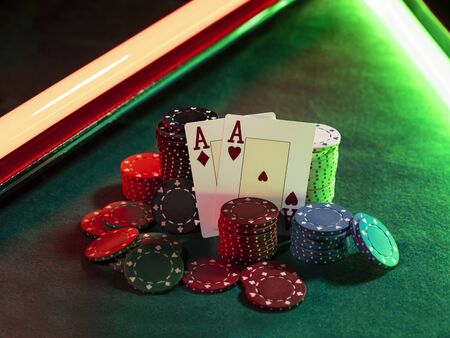 Close-up photo of two aces hearts and diamonds standing leaning on colored chips piles, some of them are laying nearby on a green cover of a playing table, against black background, under green and red neon lights. Gambling entertainment, playing cards, poker, casino concept. Stock Photo