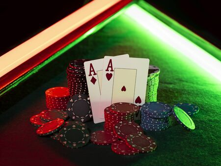 Close-up shot of two aces hearts and diamonds standing leaning on colorful chips piles, some of them are laying nearby on a green cover of a playing table, against black background, under green and red neon lights. Gambling entertainment, playing cards, poker, casino concept.