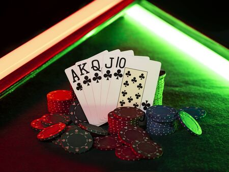 Close-up shot of the winning combination in poker standing leaning on multicolored chips piles, some of them are laying nearby on a green cover of a playing table, against black background, under green and red neon lights. Gambling entertainment, playing cards, casino concept.