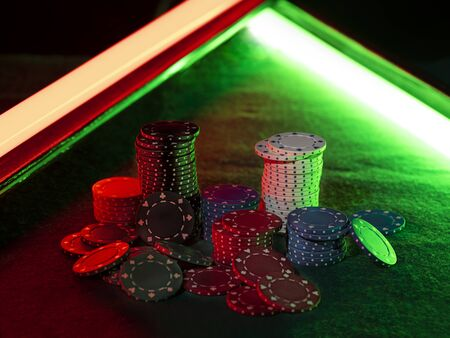 Close-up shot of a colored chips piles, some of them are laying nearby on a green cover of a playing table, against black background, under green and red neon lights. Gambling entertainment, poker, casino concept.