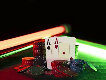 Close-up shot of two aces hearts and spades standing leaning on colorful chips piles, some of them are laying nearby on a green cover of a playing table, against black background, under green and red neon lights. Gambling entertainment, playing cards, poker, casino concept.
