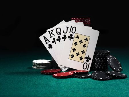 Close-up photo of royal flush standing leaning on colorful chips piles, some of them are laying nearby on a green cover of a playing table, against black background. Gambling entertainment, playing cards, casino concept.