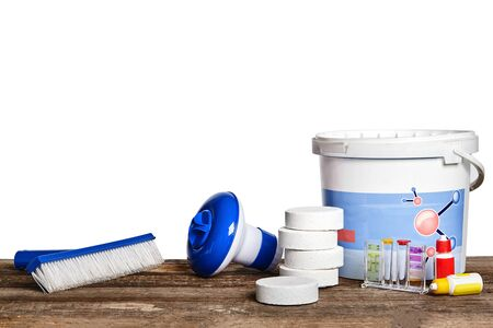 Equipment with chemical cleaning products and tools for the maintenance of the swimming pool on a wooden surface against white background. Zdjęcie Seryjne