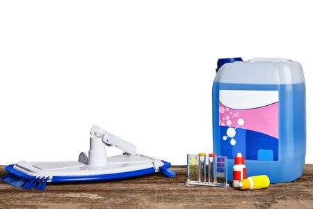 Equipment with chemical cleaning products and tools for the maintenance of the swimming pool on a wooden surface against white background. Banque d'images