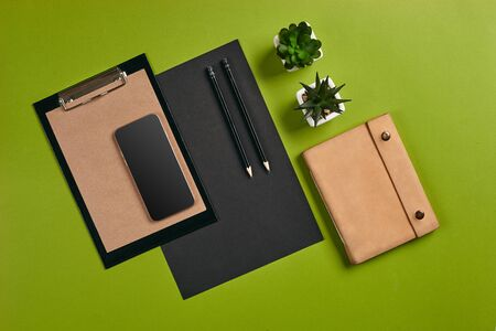 Top view in focus with different office equipment, supplies, stationery. Green background with copy space. Education, workplace concept. Close-up. 免版税图像