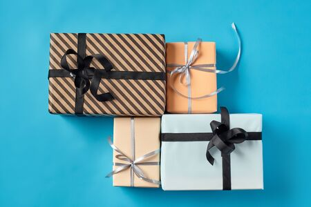 Different sizes, colorful, striped and plain, brown, pink and white paper present packages tied with black and silver ribbons and bows on a blue background. Concept of holidays, fests, celebrations, congratulations, decorations, greetings. Close-up shot. Copy space. Top view.