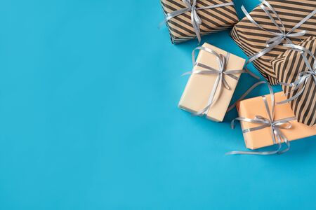 Various sized, colorful, striped and plain, brown and pink paper gift boxes tied with silver ribbons and bows on a blue background. Concept of holidays, fests, celebrations, congratulations, presents, decorations, greetings. Close-up shot. Copy space. Top view.