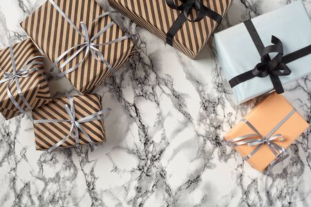 Different sizes, colorful, striped and plain, brown, pink and white paper present boxes tied with black and silver ribbons and bows on a marble background. Concept of holidays, fests, celebrations, congratulations, decorations, greetings. Close-up shot. Copy space. Top view.