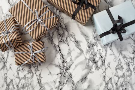 Different sizes, striped and plain, brown and white paper gift boxes tied with black and silver ribbons and bows on a marble background. Concept of holidays, fests, celebrations, congratulations, presents, decorations, greetings. Close-up shot. Copy space. Top view.