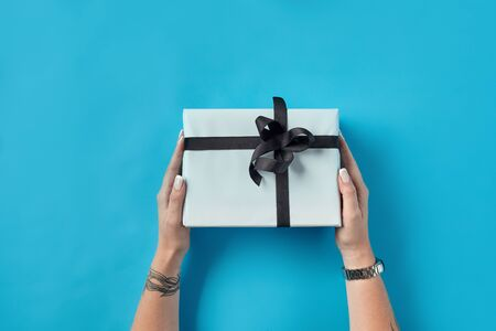 Hands of a woman with tattoes and watch are holding white paper gift box tied with black ribbon and bow on a blue background. Concept of holidays, fests, celebrations, congratulations, presents, decorations, greetings. Close-up shot. Copy space. Top view.