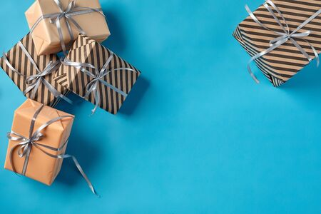 Different sizes, colorful, striped and plain, brown and pink paper present packages tied with silver ribbons and bows on a blue background. Concept of holidays, fests, celebrations, congratulations, decorations, greetings. Close-up shot. Copy space. Top view.