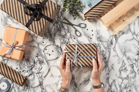 Hands of a woman are holding brown striped paper present box tied with silver ribbon and bow against a marble background. Wrapping paper, green twig, decorative little stars and scissors are laying nearby. Concept of holidays, fests, celebrations, congratulations, decorations, greetings. Close-up shot. Copy space. Top view.