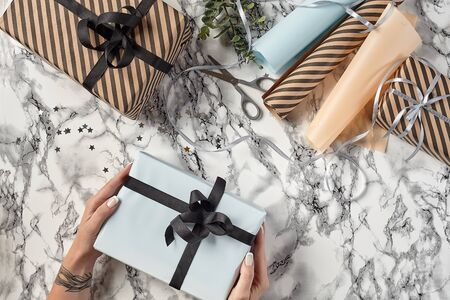 Hands of a woman are holding white paper gift box tied with black ribbon and bow against a marble background. Wrapping paper, decorative little stars, green twig and scissors are laying nearby. Concept of holidays, fests, celebrations, congratulations, presents, decorations, greetings. Close-up shot. Copy space. Top view.