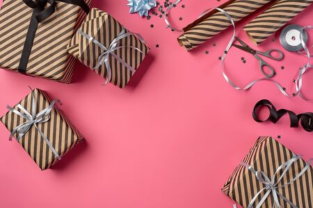 Various sized, striped, brown gift boxes tied with black and silver ribbons and bows on a pink background. Wrapping paper and metal scissors are laying nearby. Concept of holidays, fests, celebrations, congratulations, presents, decorations, greetings. Close-up shot. Copy space. Top view. Stock fotó