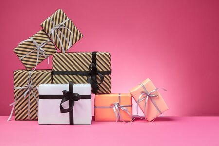 Different sized, colorful, striped and plain, brown, rose and white paper gift boxes tied with colored ribbons and bows on a pink surface and background. Concept of holidays, fests, celebrations, congratulations, presents, decorations, greetings. Close-up shot. Copy space. Stock fotó