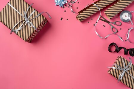 Different sizes, striped, brown present boxes tied with black and silver ribbons and bows on a pink background. Wrapping paper, decorative stars and scissors are laying nearby. Concept of holidays, fests, celebrations, congratulations, decorations, greetings. Close-up shot. Copy space. Top view.