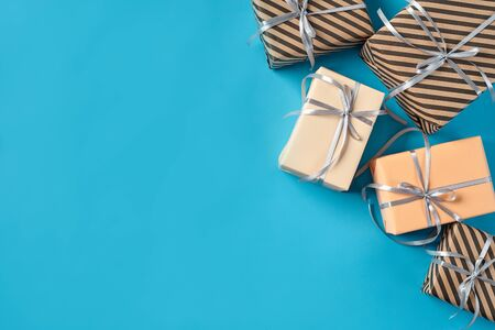 Different sizes, colorful, striped and plain, brown, pink and white paper gift boxes tied with black and silver ribbons and bows on a blue background. Concept of holidays, fests, celebrations, congratulations, presents, decorations, greetings. Close-up shot. Copy space. Top view. Stock fotó