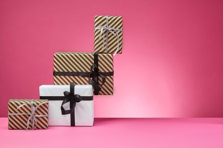 Various sized, striped and shadeless, brown and white paper gift boxes tied with black and silver ribbons and bows standing on a pink surface and background. Concept of holidays, fests, celebrations, congratulations, presents, decorations, greetings. Close-up shot. Copy space.