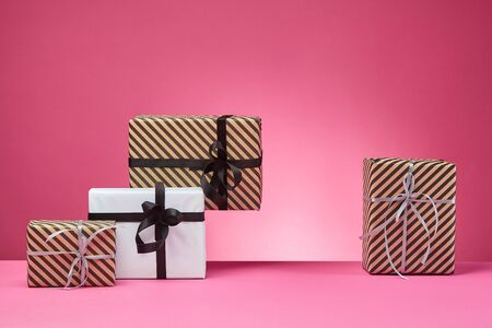 Various sized, striped and plain, brown and white gift boxes tied with black and silver ribbons and bows standing on a pink table and background. Concept of holidays, fests, celebrations, congratulations, presents, decorations, greetings. Close-up shot. Copy space.